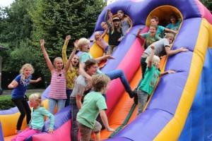 Kinderen stoeien op een luchtkussen/ stormbaan bij hun Oisterwijks buurtfeest. (