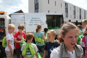 Kinderen brengen het vuil naar de wagen van de gemeente. (foto Petra Wevers)