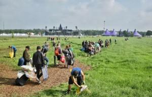Groepen bezoekers trekken door het naastgelegen weiland richting festivalterrein van Intents Oisterwijk (Foto: Toby de Kort).