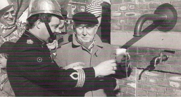 Barman en brandweerman Ad, tapt als eerste een glasje bij de vorige ondertussen afgebroken Dorpspomp...